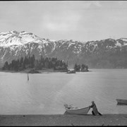 Cover image of Man launching boat on unidentified lake