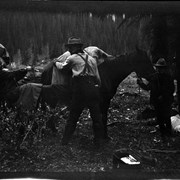 Cover image of Elliott Barnes and unidentified woman packing horse