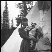 Cover image of Unknown woman holding baby outside teepee