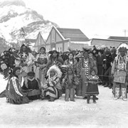 Cover image of Ben and Janet Kaquitts standing on the left in regalia, Mark Poucette standing to the right in regalia, Stoney Nakoda