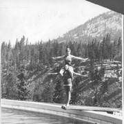 Cover image of Banff, Canada. Banff Springs Hotel Pool. Miss Catherine Barber of Chicago doing aeroplane dive. Background Cascade Mt / 27033