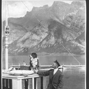 "Cover image of Banff, Canada. Captain John Standly and Peter, his black and white collie, on the deck of his boat, ""The Daughter of the Peaks."" Lake Minnewanka, Indian name, ""Spirit Water"", near Banff / 27036"