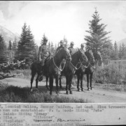 "Cover image of Banff, mounted police, summer uniform, red coat, blue trousers. These men are constables: F. W. Wood, riding ""Pete""; W. Neish, riding ""Crazy""; W. Hile, riding ""Kitchner""; E. L. Stapleton, riding ""Brownie"". Enfield Carbine is used and colts 45-6 shooter / 27689"