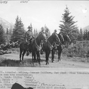 "Cover image of Banff, mounted police, summer uniform, red coat, blue trousers. These men are constables: F. W. Wood, riding ""Pete""; W. Neish, riding ""Crazy""; W. Hile, riding ""Kitchner""; E. L. Stapleton, riding ""Brownie"". Enfield Carbine is used and colts 45-6 shooter / 27695"