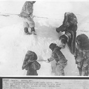 Cover image of Canada. Hudson Bay. Esquimo family building their igloo. The man and woman on the roof are filling in with snow the chinks between the blocks of ice. Below, the boy is closing the door / 38885
