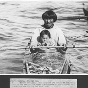 Cover image of Canada. Hudson Bay. Father and son. This Esquimo has taken his child out to sea in his kayak (canoe made of seal hides) to teach him how to jig for rock cod / 38879