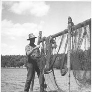 Cover image of An old Nova Scotia fisherman mending his nets while they dry in the sun on Nova Scotia's South shore / CN284